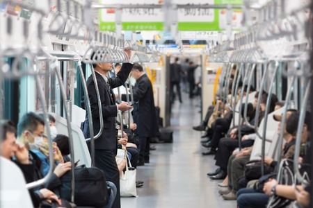 Passengers traveling by Tokyo metro. Business people commuting to work by public transport in rush hour. Shallow depth of field photo. Standard-Bild