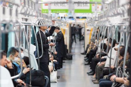 Passagerare som reser med Tokyo tunnelbanan. Affärsmän som pendlar till arbete med kollektivtrafik i rusningstid. Grunt skärpedjup foto.