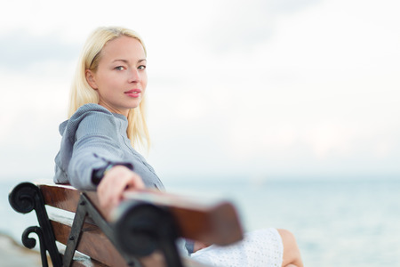 woman looking: Beautiful woman sitting on a vintage wooden bench, relaxing on fresh breeze by the sea, looking at camera.