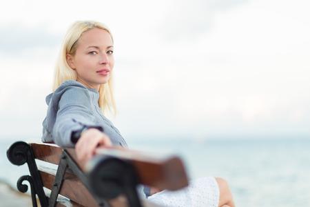 mujer mirando el horizonte: Hermosa mujer sentada en un banco de madera de la vendimia, se relaja en la brisa fresca del mar, mirando a la cámara.