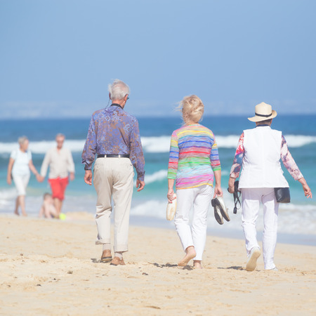 ageing: Active seniors enjoying beach walk. Active ageing, healthy lifestyle and well-being throughout life course concept.
