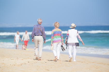 Active seniors enjoying beach walk. Active ageing, healthy lifestyle and well-being throughout life course concept.