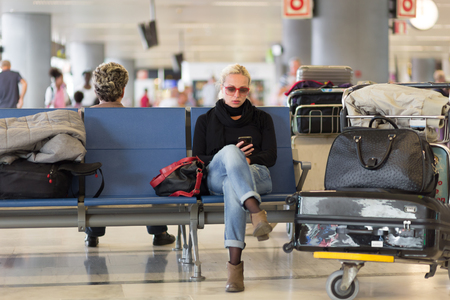enabling: Casual blond young woman using her cell phone while waiting to board a plane at the departure gates. Wireless network hotspot enabling people to access internet conection. Public transport.