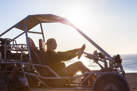 quad: Active woman driving quadbike on dirt road by the sea in sunset.