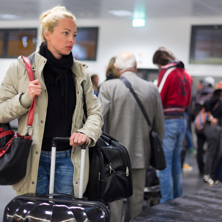 be dressed in: Casually dressed young female traveller waiting in airport arrival terminal hall,  collecting her laggage . Blured background. Can also be used as railway, metro, bus station.