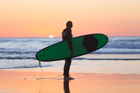 male surfer: Silhouette of male surfer on the beach with the surfboard watching sunset.
