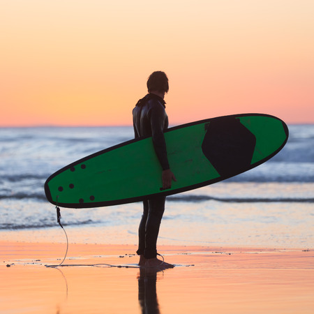 square composition: Silhouette of male surfer on the beach with the surfboard watching sunset. Square composition. Stock Photo