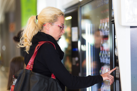 Casual caucasian woman using a modern beverage vending machine. Her hand is placed on the dial pad and she is looking on the small display screen.