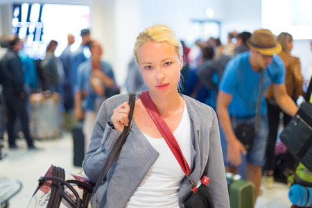 be dressed in: Casually dressed young stylish female traveller waiting in airport arrival terminal hall,  collecting her laggage . Blured background. Can also be used as railway, metro, bus station. Stock Photo