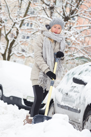 snowstorm: Independent woman shoveling her parking lot after a winter snowstorm.