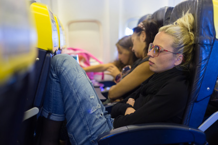 People flying by plane. Interior of airplane with passengers sleeping on seats. Tired woman napping on uncomfortable seat on airplane. Commercial transportation by planes.