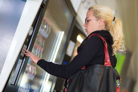 vending: Casual caucasian woman using a modern beverage vending machine. Her hand is placed on the dial pad and she is looking on the small display screen.