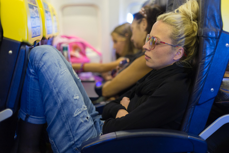 People flying by plane. Interior of airplane with passengers sleeping on seats. Tired woman napping on uncomfortable seat on airplane. Commercial transportation by planes. Stock Photo - 53608790