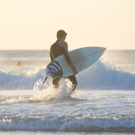 Male surfer on the beach with the surfboard in sunset. Square composition. Stock Photo