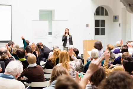 Ho una domanda. Gruppo di persone sedute a sedie in sala conferenze, alzando la mano. Workshop presso l'università. Affari e evento imprenditorialità. Archivio Fotografico