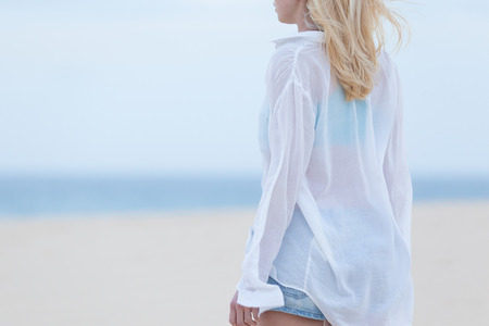 white shirt: Sensual blonde woman wearing white loose casual shirt on vacations looking down sandy beach in dusk.