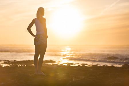 mujer mirando el horizonte: Silueta de la meditaci�n, sensual mujer rubia viendo la puesta de sol en la playa.