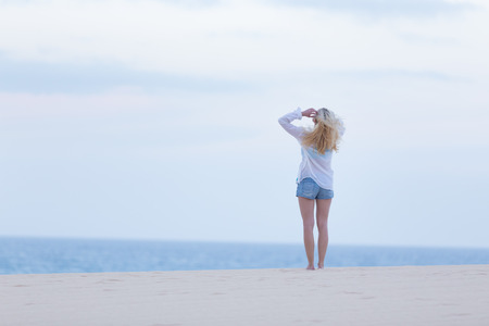 meditative: Meditative, sensual blonde woman wearing white loose casual shirt on vacations looking at horizon at dusk.