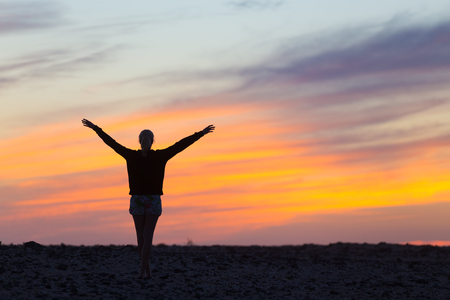 feeling happy: Silhouette of free woman enjoying freedom feeling happy at sunset. Serene relaxing woman in pure happiness and elated enjoyment with arms raised outstretched up. Stock Photo