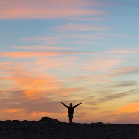 mujer mirando el horizonte: Silueta de la mujer libre que disfruta de la libertad que siente feliz al atardecer. mujer que se relaja en la serena felicidad pura y disfrute euf�rico con los brazos levantados extendidos hacia arriba. Foto de archivo
