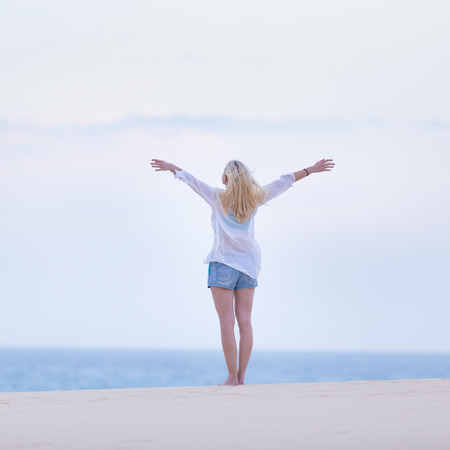 feeling happy: Relaxed woman enjoying freedom feeling happy at beach in the morning. Serene relaxing woman in pure happiness and elated enjoyment with arms raised outstretched up.