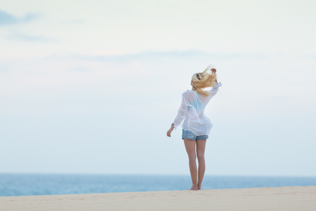 meditative: Meditative, sensual blonde woman wearing white loose casual shirt on vacations, looking at horizon, enjoying peaceful early morning.