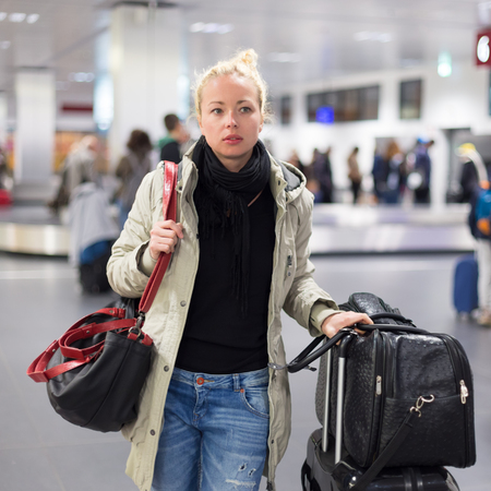 be dressed in: Casually dressed young female traveller walking in airport terminal hall with collected laggage after flight arrival . Blured background. Can also be used as railway, metro, bus station.