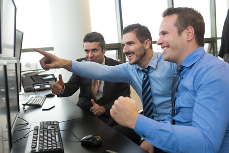 indexes: Successful businessmen trading stocks. Stock traders looking at graphs, indexes and numbers on multiple computer screens. Colleagues in traders office. Business success. Stock Photo