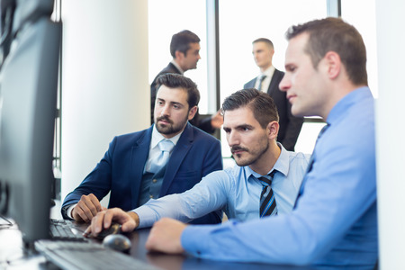 stock traders: Business team working in corporate office. Businessmen trading stocks. Stock traders looking at graphs, indexes and numbers on multiple computer screens. Business success concept.
