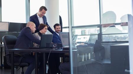 En milieu de travail dans le bureau moderne avec des gens d'affaires de remue-méninges. Homme d'affaires travaillant sur un ordinateur portable lors de la réunion.