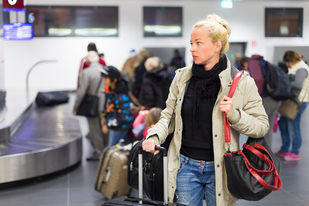 be dressed in: Casually dressed young female traveller waiting in airport arrival terminal hall,  collecting her luggage . Blurred background. Can also be used as railway, metro, bus station. Stock Photo