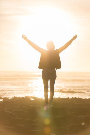 mujer mirando el horizonte: Silueta de la mujer libre, exento sentirse feliz en la playa al atardecer. mujer que se relaja en la serena felicidad pura y disfrute euf�rico con los brazos levantados extendidos hacia arriba.