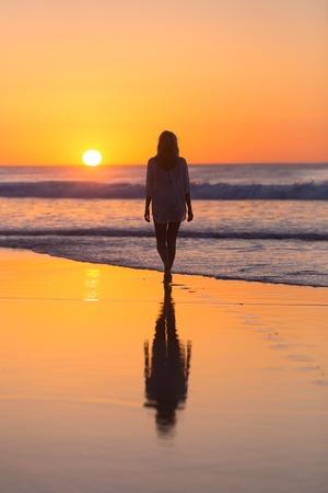 砂の夕日去る足跡の砂浜の上を歩く女性。ビーチ、旅行、コンセプト。領域をコピーします。垂直方向の組成物。
