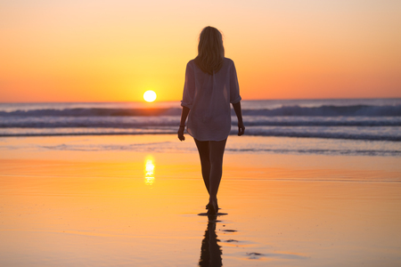 woman alone: Woman walking on sandy beach in sunset leaving footprints in the sand. Beach, travel, concept. Copy space. Vertical composition. Stock Photo
