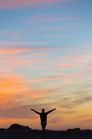 elated: Silhouette of free woman enjoying freedom feeling happy at sunset. Serene relaxing woman in pure happiness and elated enjoyment with arms raised outstretched up. Stock Photo