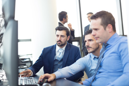 stock traders: Business team working in corporate office. Businessmen trading stocks. Stock traders looking at data on multiple computer screens. Business success concept.