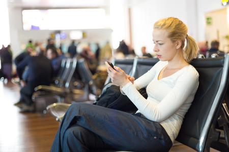 conection: Casual blond young woman using her cell phone while waiting to board a plane at the departure gates. Wireless network hotspot enabling people to access internet conection. Public transport.