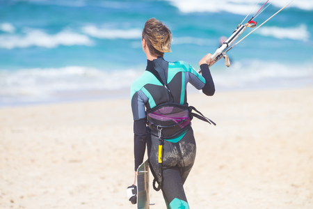 kiteboarding: Sporty fit female kiteboarder walking in water with lunched kite and holding her board to start kiteboarding session.