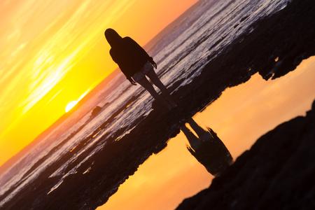 mujer mirando el horizonte: Silueta de la meditación, sensual mujer rubia viendo la puesta de sol en la playa.