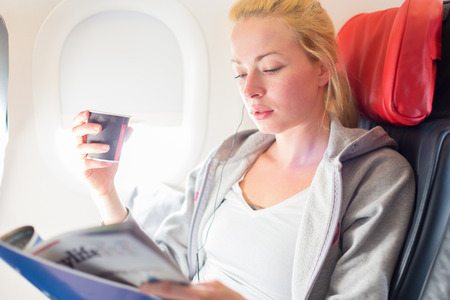 Woman reading magazine and drinking coffeeon airplane. Female traveler reading seated in passanger cabin. Sun shining trough airplane window.