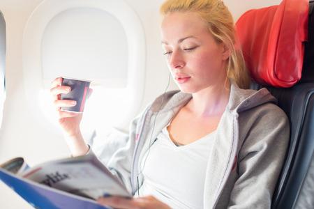 tomando café: Mujer leyendo la revista y beber avión coffeeon. lectura femenino viajero sentado en la cabina del pasajero. Sun que brilla a través la ventana del avión. Foto de archivo