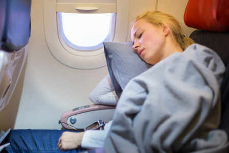 Tired blonde casual caucasian lady napping on uncomfortable seat while traveling by airplane. Commercial transportation by planes. Фото со стока - 54811484