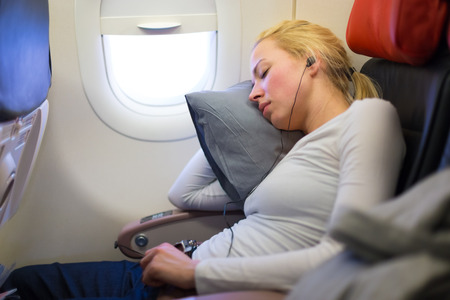 uncomfortable: Tired blonde casual caucasian lady listens to music while napping on uncomfortable seat while traveling by airplane. Commercial transportation by planes. Stock Photo