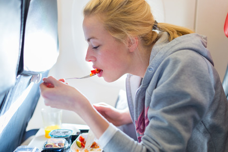 Woman eating meal on commercial airplane. Stock Photo - 54811486