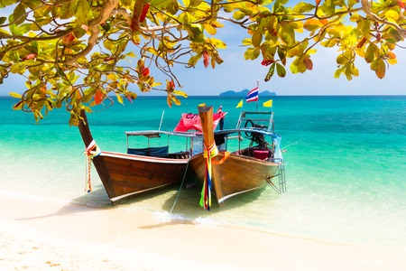 thailand beach: Traditional wooden long tail boats on a picture perfect tropical beach near Phuket, Thailand, Asia.