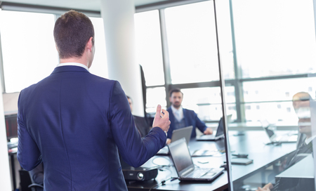 CONFERENCE TABLE: Business man making a presentation at office. Business executive delivering a presentation to his colleagues during meeting or in-house business training, explaining business plans to his employees. Stock Photo