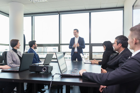 Successful team leader and business owner  leading in-house business meeting, explaining business plans to his employees. Business and entrepreneurship concept. Stock Photo