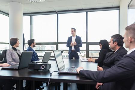 Succesvolle teamleider en ondernemer toonaangevende in-house zakelijke bijeenkomst, uit te leggen bedrijfsplannen aan zijn werknemers. Bedrijfsleven en ondernemerschap concept.