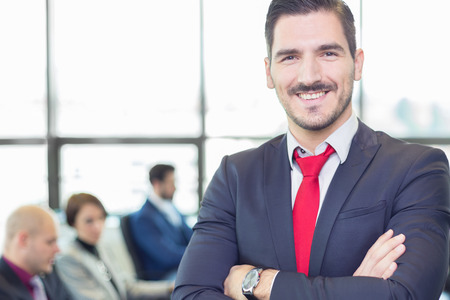 group meeting: Successful team leader and business owner proudly standing with crossed arms with  coworkers working in office in background. Business and entrepreneurship concept. Stock Photo