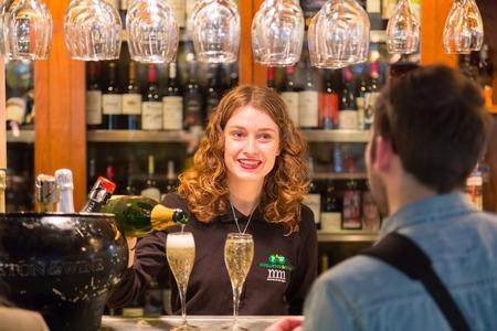 socializando: Madrid, España - 25 Ene, 2016: Camarera que sirve champán en el Mercado San Miguel el 25 de enero, 2016, Madrid, España. Es uno de los principales destinos personas que socializan en Madrid. Editorial